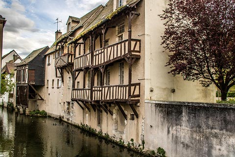 Ancient houses with balconies on river in Montargis