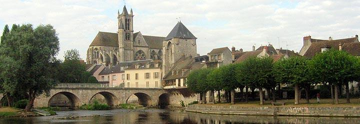 view of Moret-sur-Loing, with Loing river, old bridge, medieval entry tower and Church of Notre-Dame