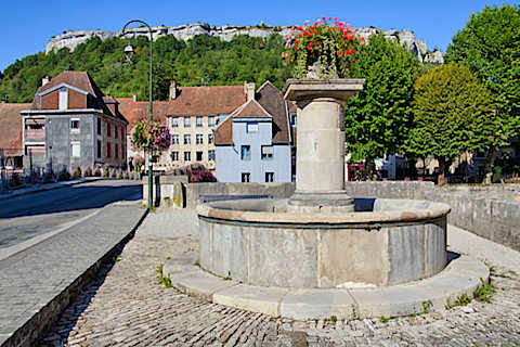Fontaine traditionnelle à côté du pont à Ornans
