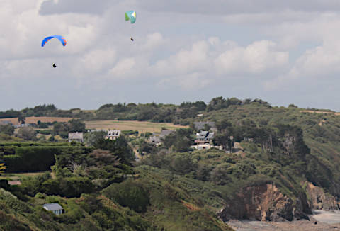 View of hang-gliders along the coast from the belvedere at Pointe du Roselier